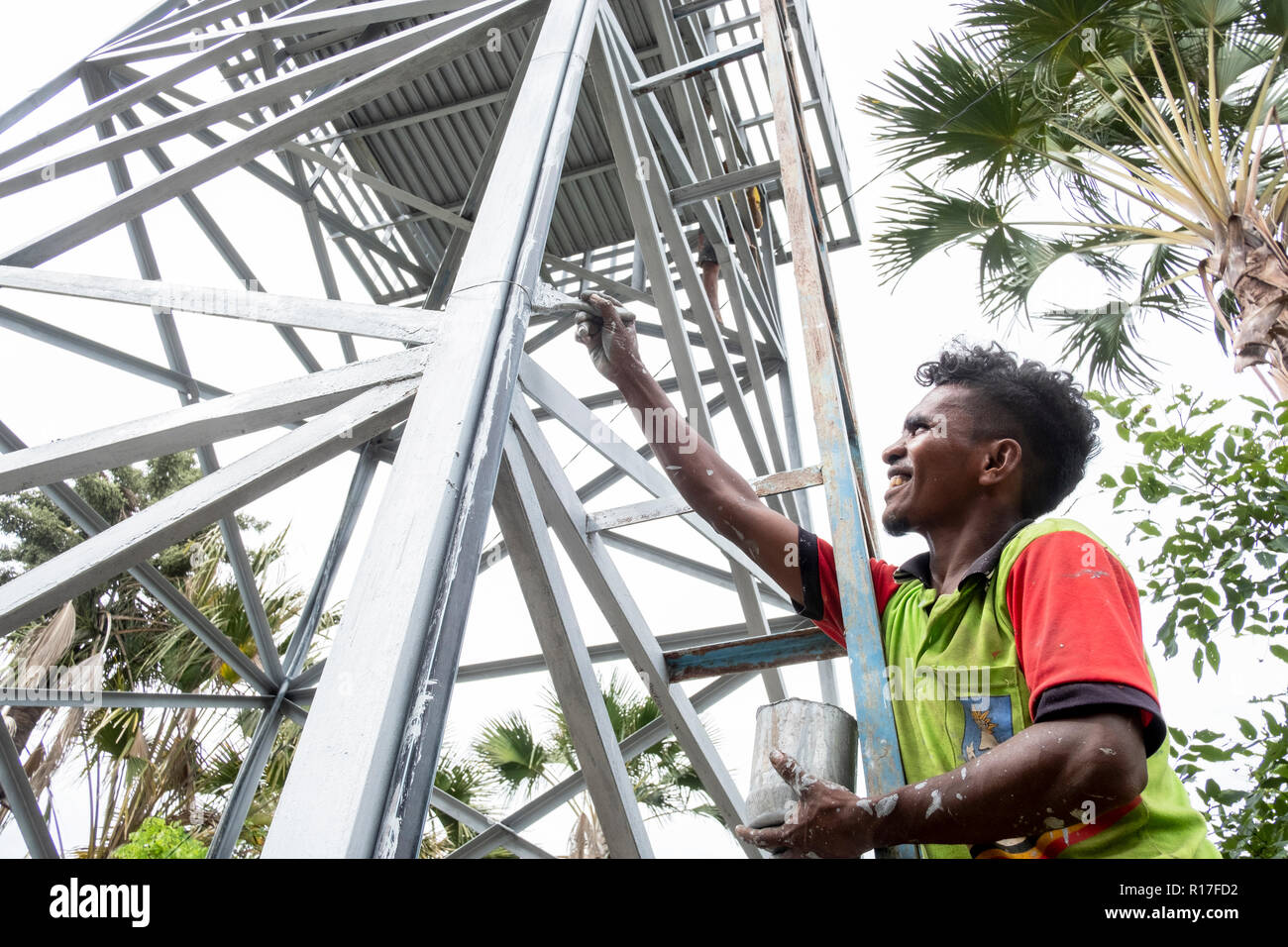A villager paints a new water tower in Kasait, Liquica, Timor-Leste. This has enabled the villagers to have fresh water for the first time. Stock Photo