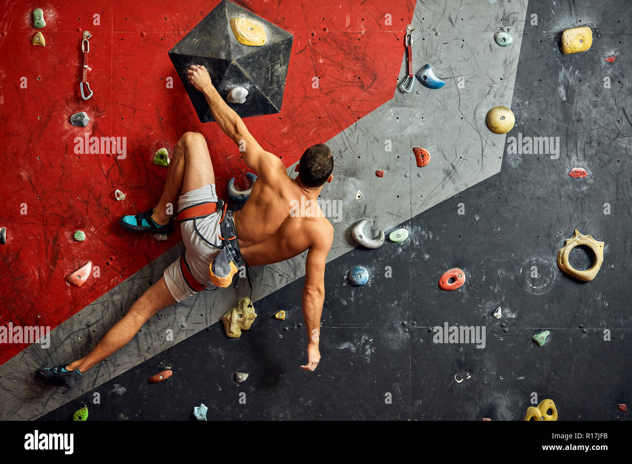 Male professional climber at indoor workout at bouldering centre. Stock Photo
