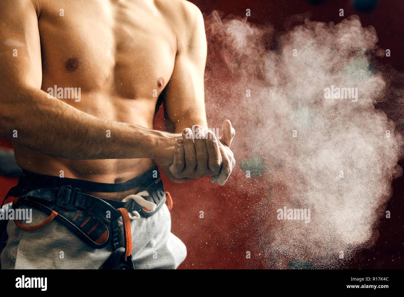Man coating his hands in powder chalk magnesium preparing to climb, motion Stock Photo