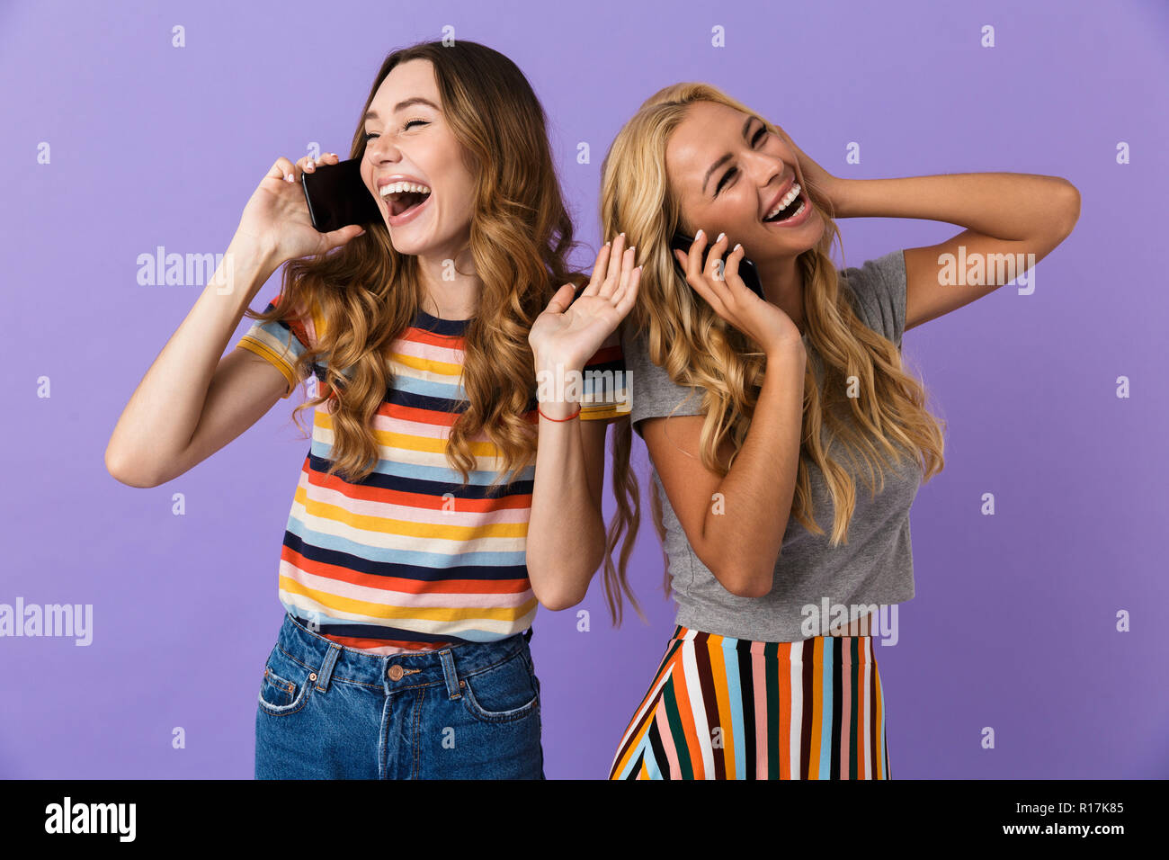 Two pretty laughing young girls friends standing isolated