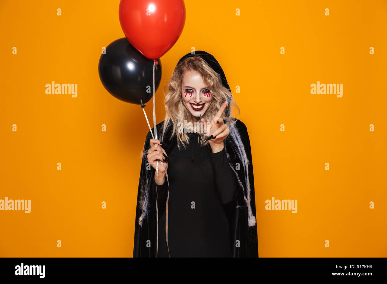 Tricky scary witch in black clothes looking camera with red and black air balloons isolated - Stock Image