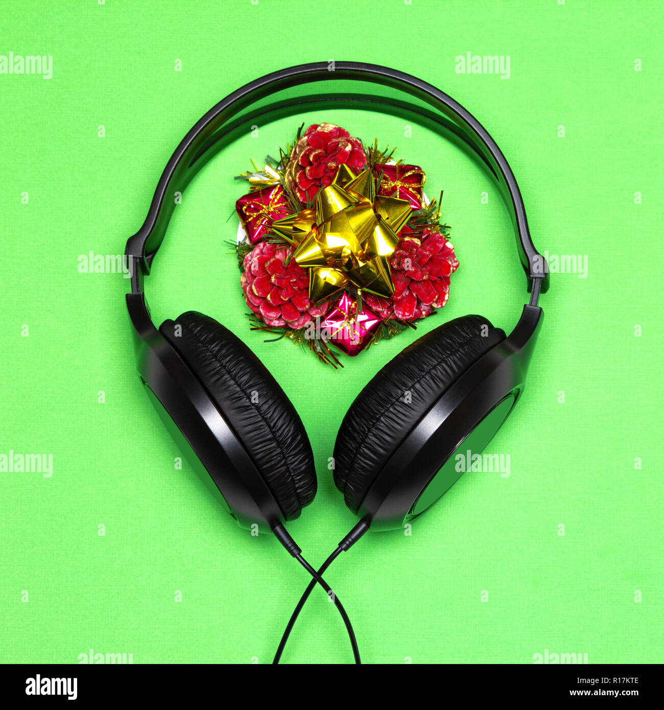 Headphones and New Year decorations. Christmas party music playlist. Xmas songs minimal concept - Stock Image