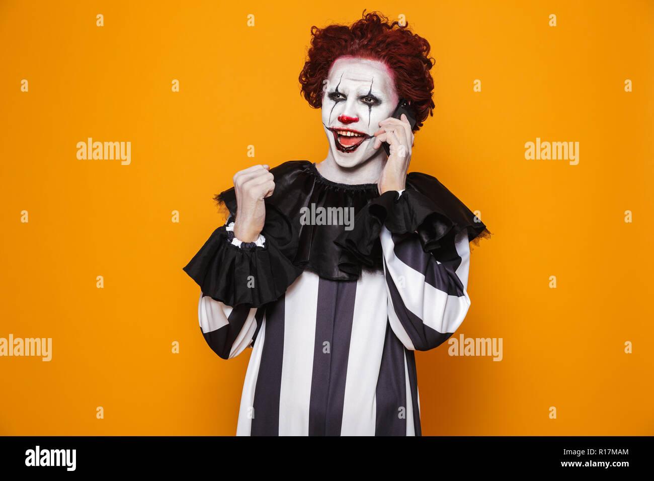 Joyful clown man 20s wearing black costume and halloween makeup talking on smartphone isolated over yellow background Stock Photo