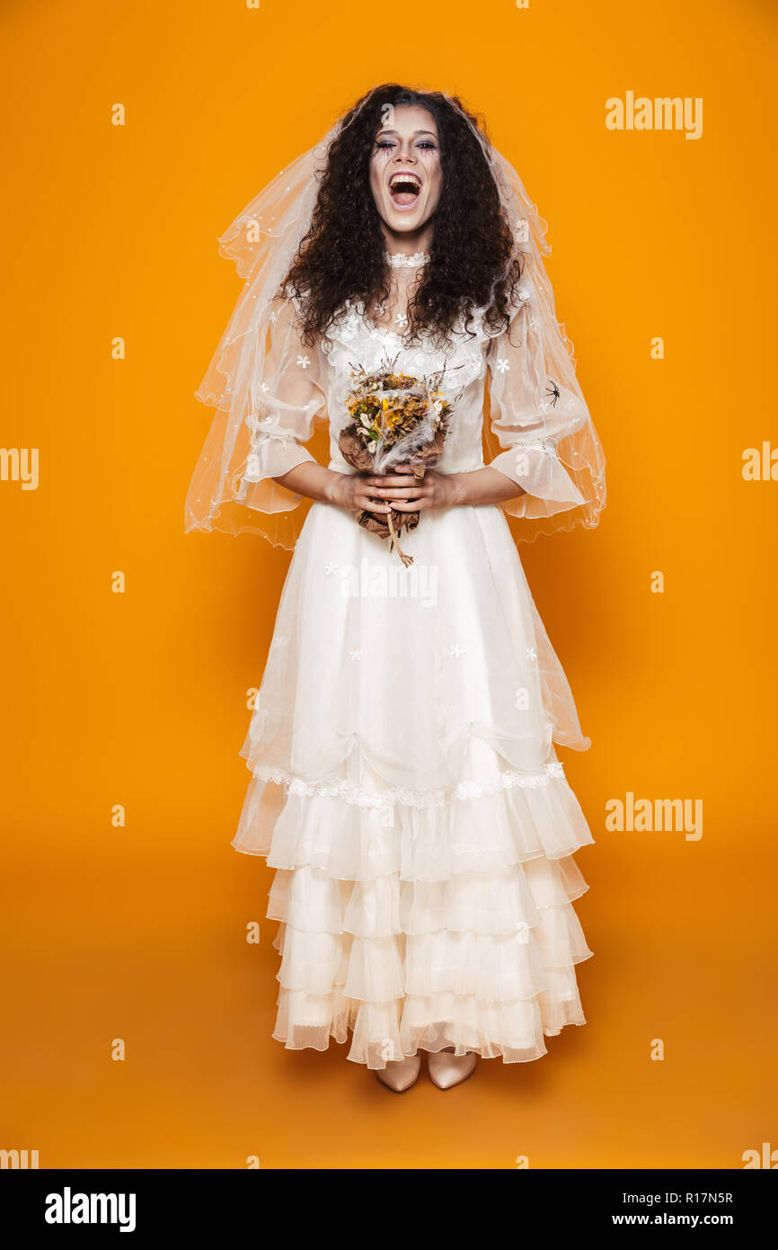 Full Length Image Of Beautiful Bride Zombie On Halloween Wearing Wedding  Dress And Scary Makeup Holding Dead Flowers Isolated Over Yellow Background