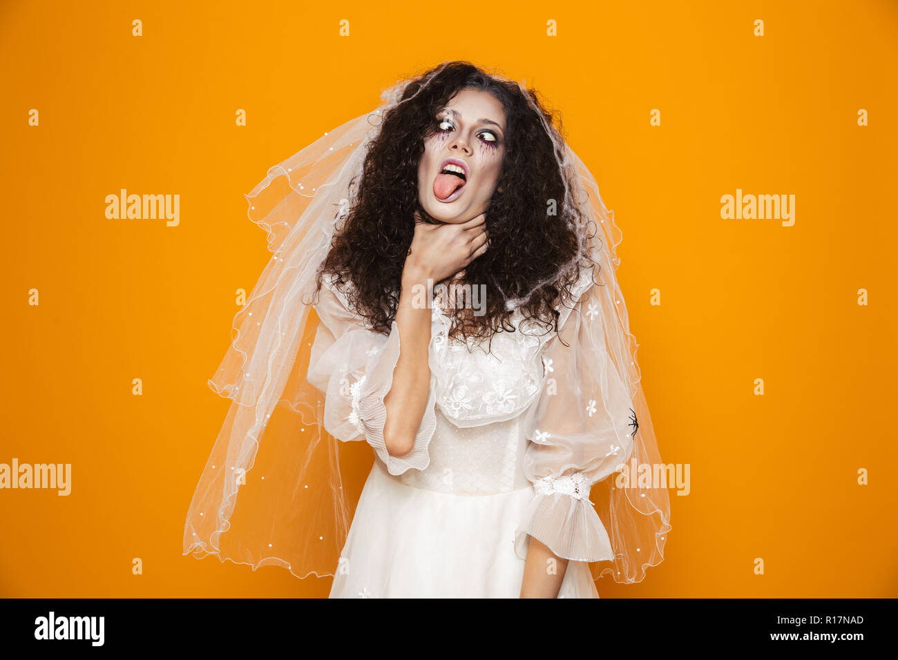 Image of dead bride zombie on halloween wearing wedding dress and scary makeup choking herself isolated over yellow background - Stock Image