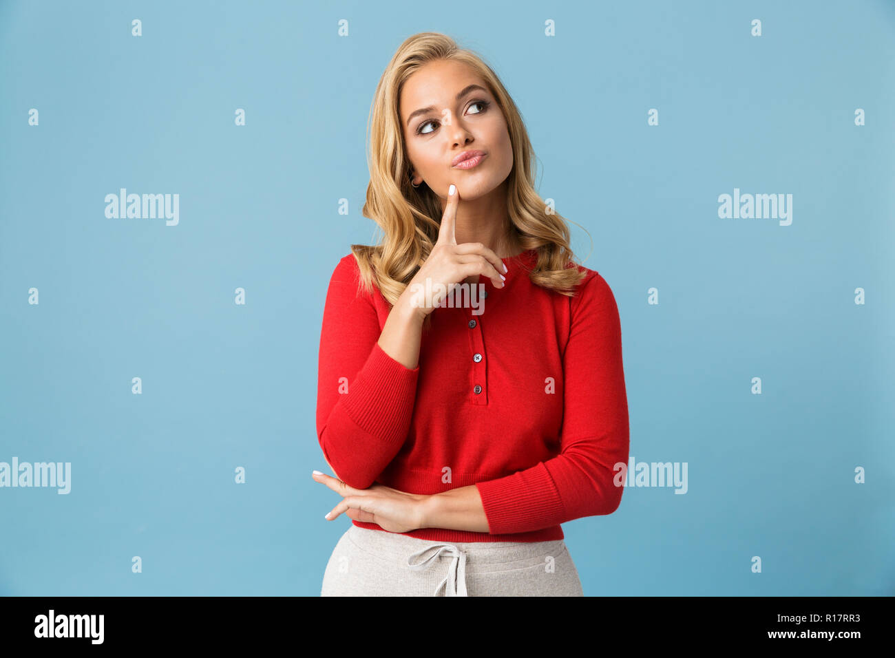 Portrait of affable blond woman 20s wearing red shirt looking aside at copyspace isolated over blue background in studio - Stock Image