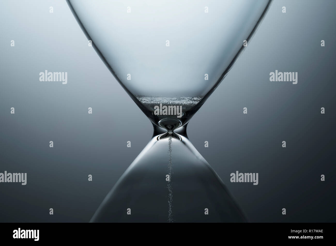 Close up view of white sand trickling through contemporary hourglass, plain background - Stock Image