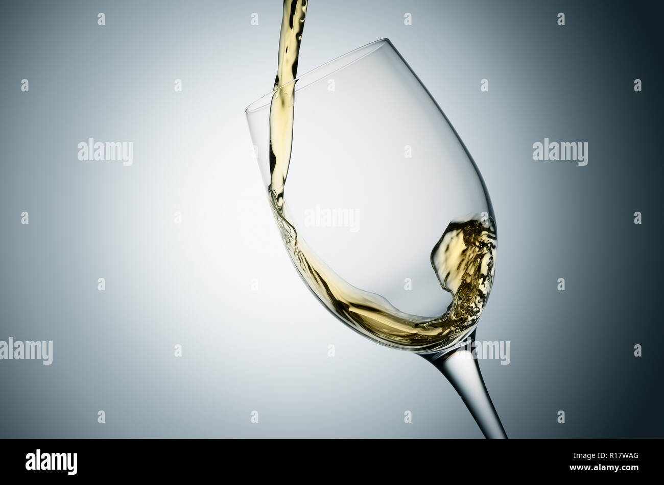 Pouring white wine into tilted glass, plain background - Stock Image