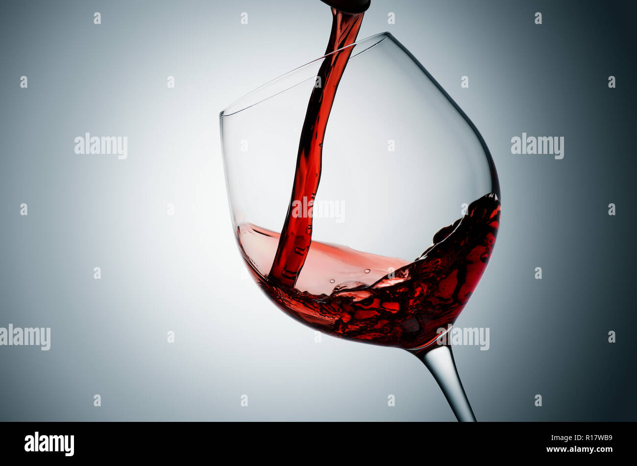 Pouring red wine into tilted glass, plain background - Stock Image