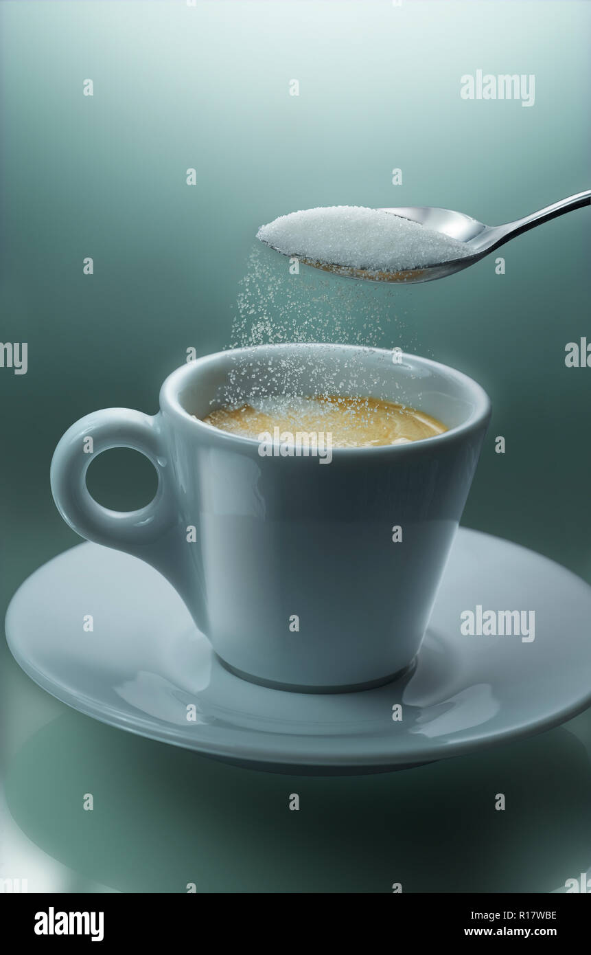 Pouring sugar from teaspoon into cup of coffee, plain background - Stock Image