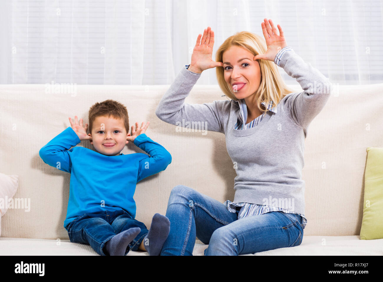 Mother and son are sitting on sofa and sticking out tounge. - Stock Image