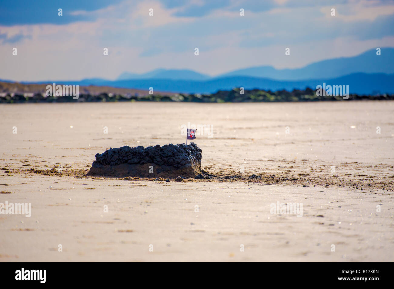 Sand castle/Mud castle topped with a small skull & crossbones flag on the beach. The mountains of Snowdoncan be seen in the background. Prestatyn, Nor Stock Photo