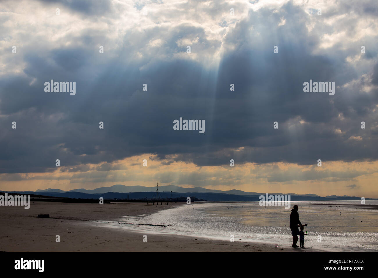 Empty beach on a gloomy moody day with sun beams coming through the stormy clouds.  Prestatyn and the mountains of Snowdonia are visible in the backgr Stock Photo