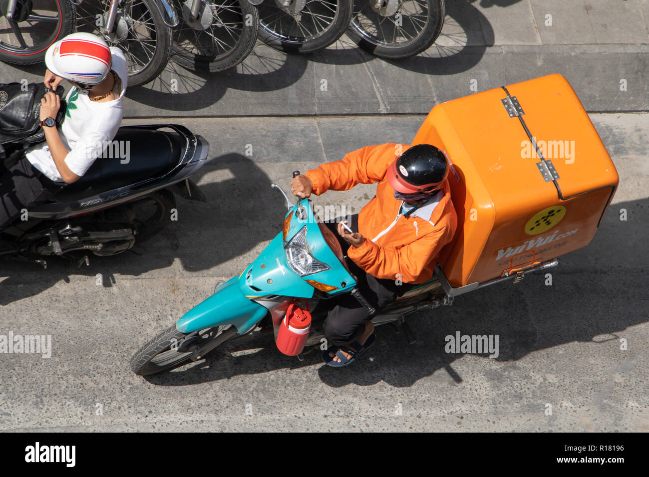 SAIGON, VIETNAM, DEC 18 2017. Motorcyclist with large orange box on bike is looking to display of phone when rides  for delivery at Saigon city, - Stock Image