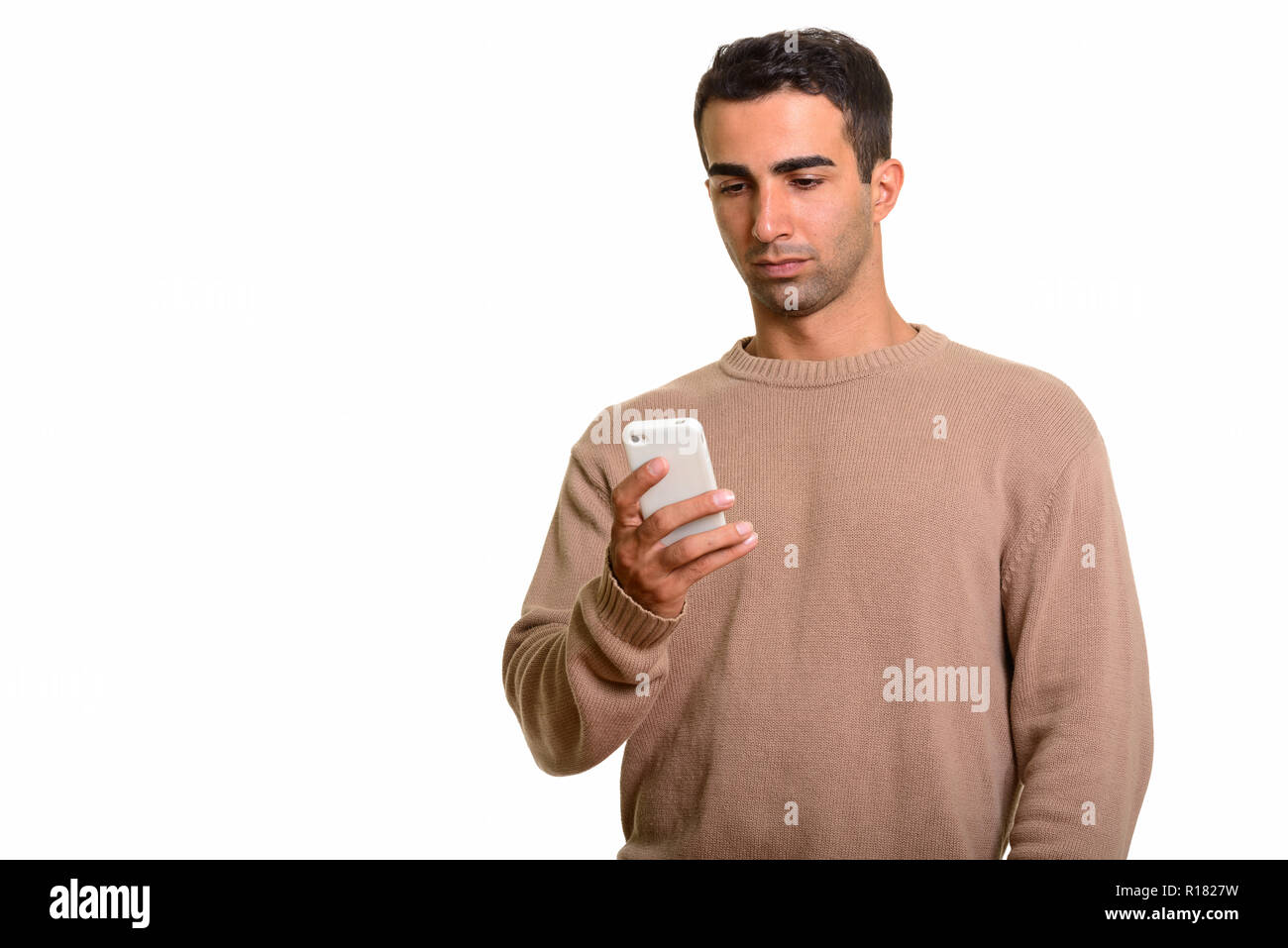 Portrait of young handsome Persian man using mobile phone Stock Photo