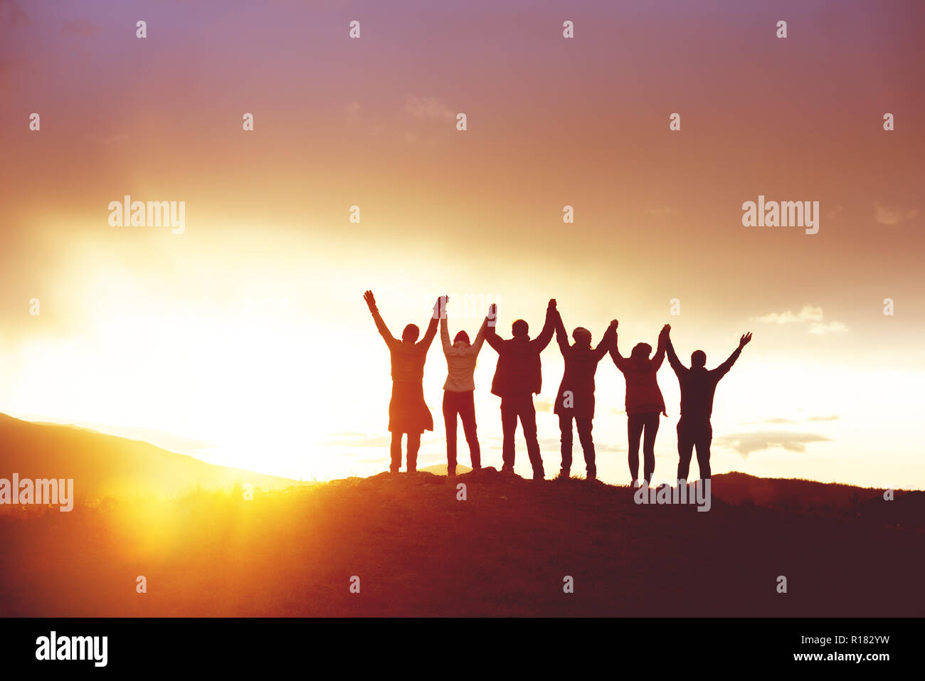 Big group of happy friends with raised hands at sunset  People's