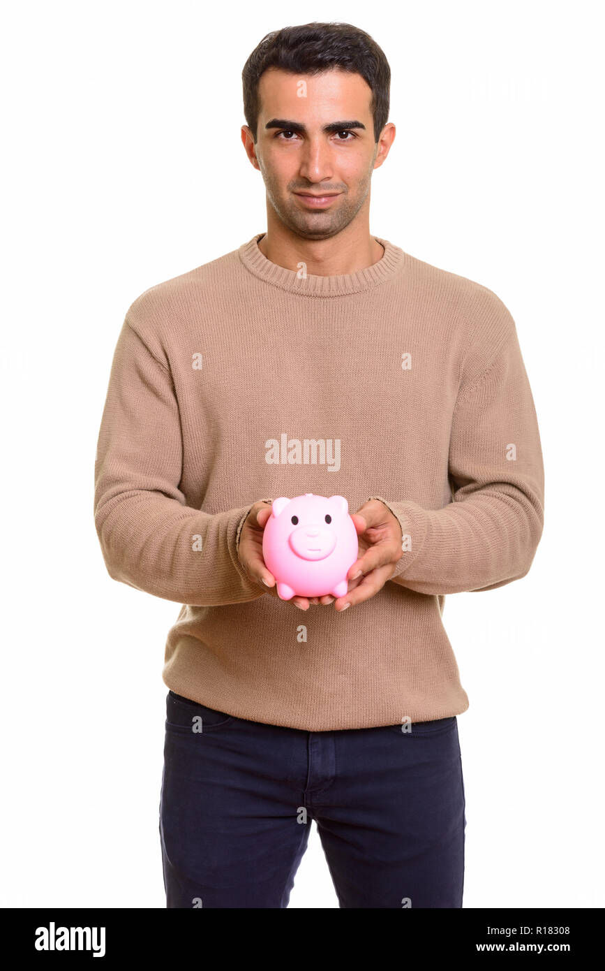 Portrait of young handsome Persian man with piggy bank - Stock Image