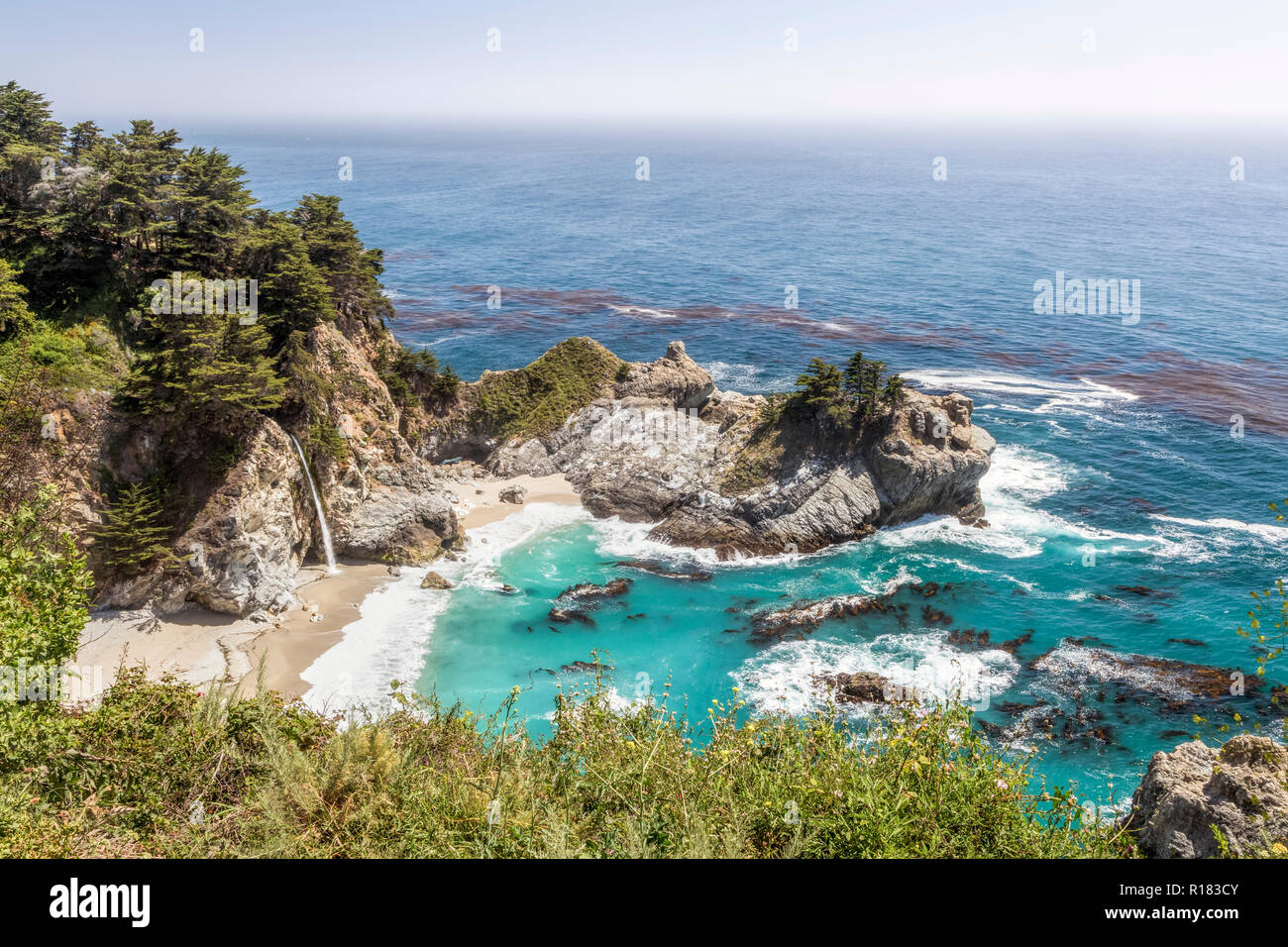 McWay Falls plunges onto a sandy beach in a beautiful rocky cove on the Big Sur Pacific Coast of California. - Stock Image