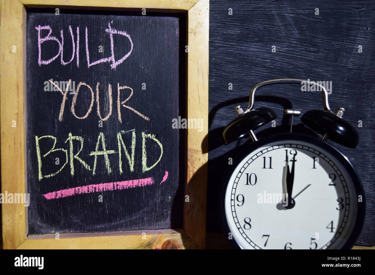 Build your brand on phrase colorful handwritten on blackboard. Education and business concept. Alarm clock, chalk, books on black background - Stock Image