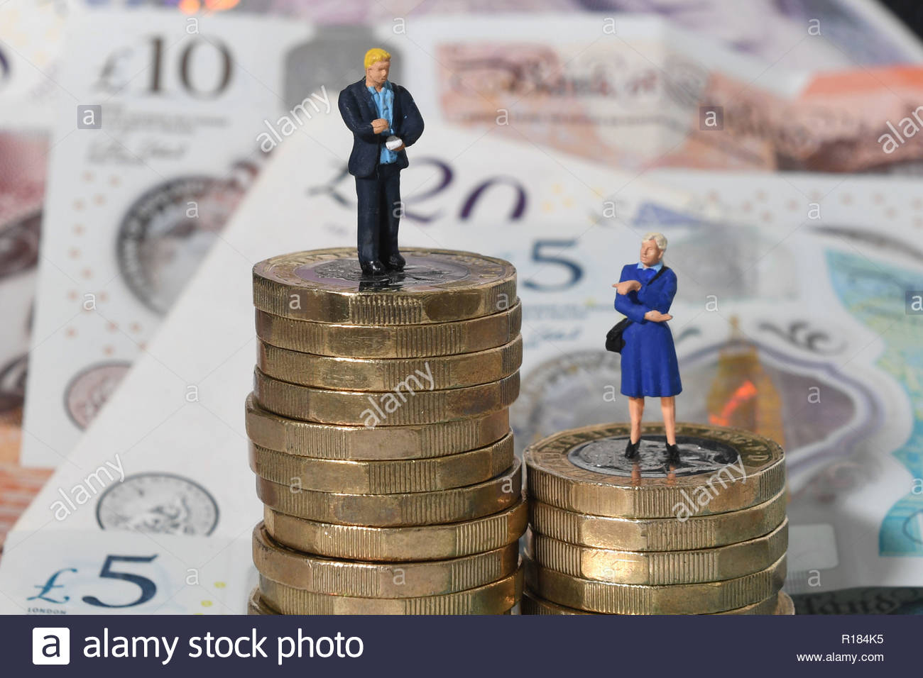 File photo dated 11/09/18 of models of a man and woman on a pile of coins and bank notes. Calls for more action to tackle the gender pay gap are being stepped up amid new research showing that women are more likely to be in low paid jobs. - Stock Image