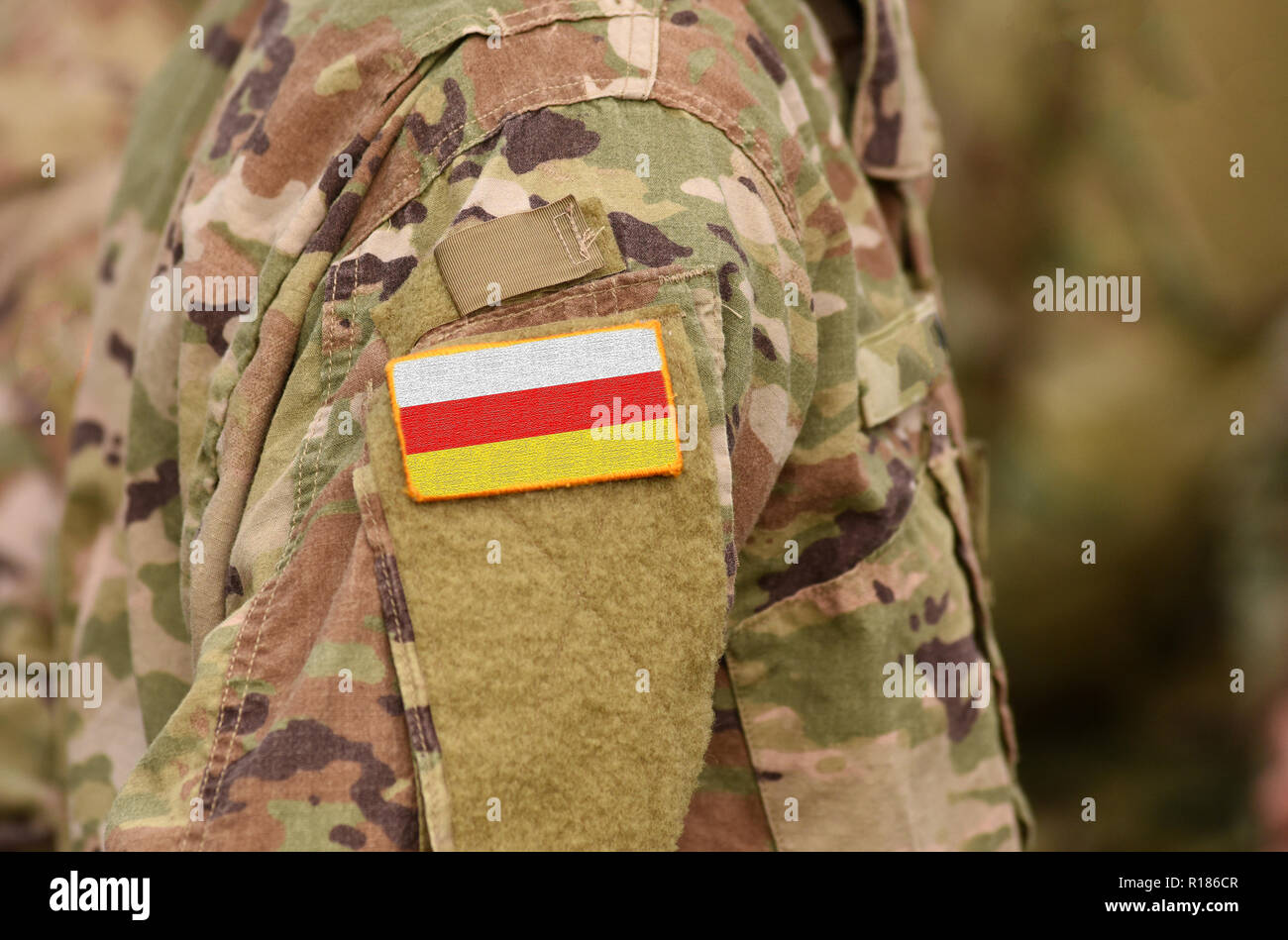 South Ossetia flag on soldiers arm. South Ossetia troops (collage) - Stock Image