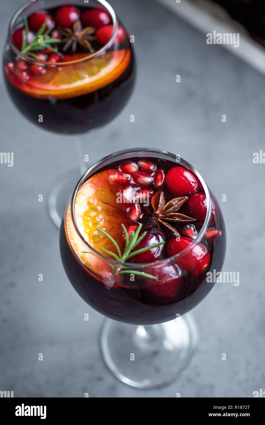 Christmas sangria with oranges, pomegranate seeds, cranberry, rosemary and spices - homemade festive drink mulled wine for Christmas time. - Stock Image