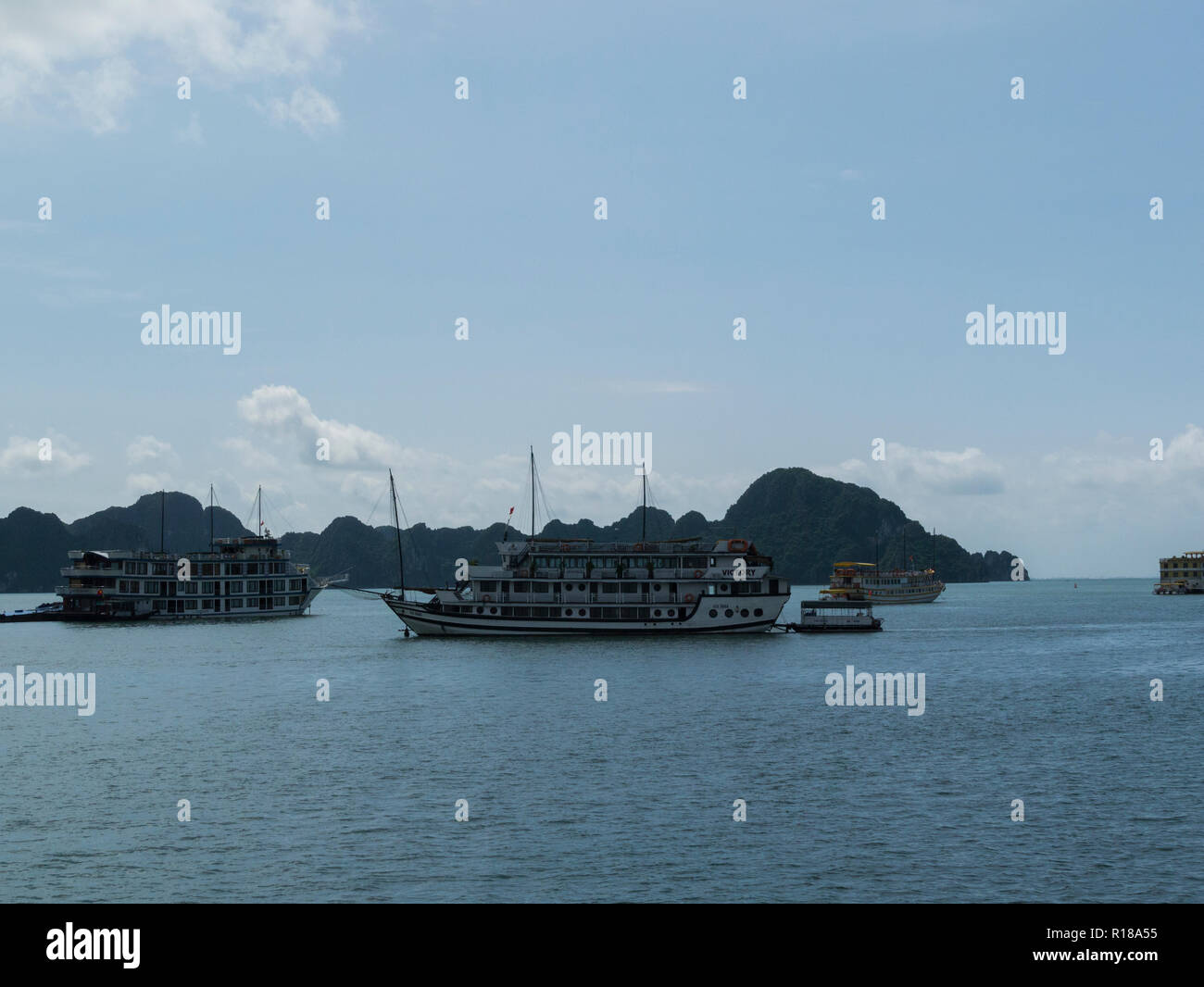 Junk boats tourist cruise in emerald waters of Halong Bay South China Sea Vietnam Asia with limestone island peaks covered in jungle foliage - Stock Image