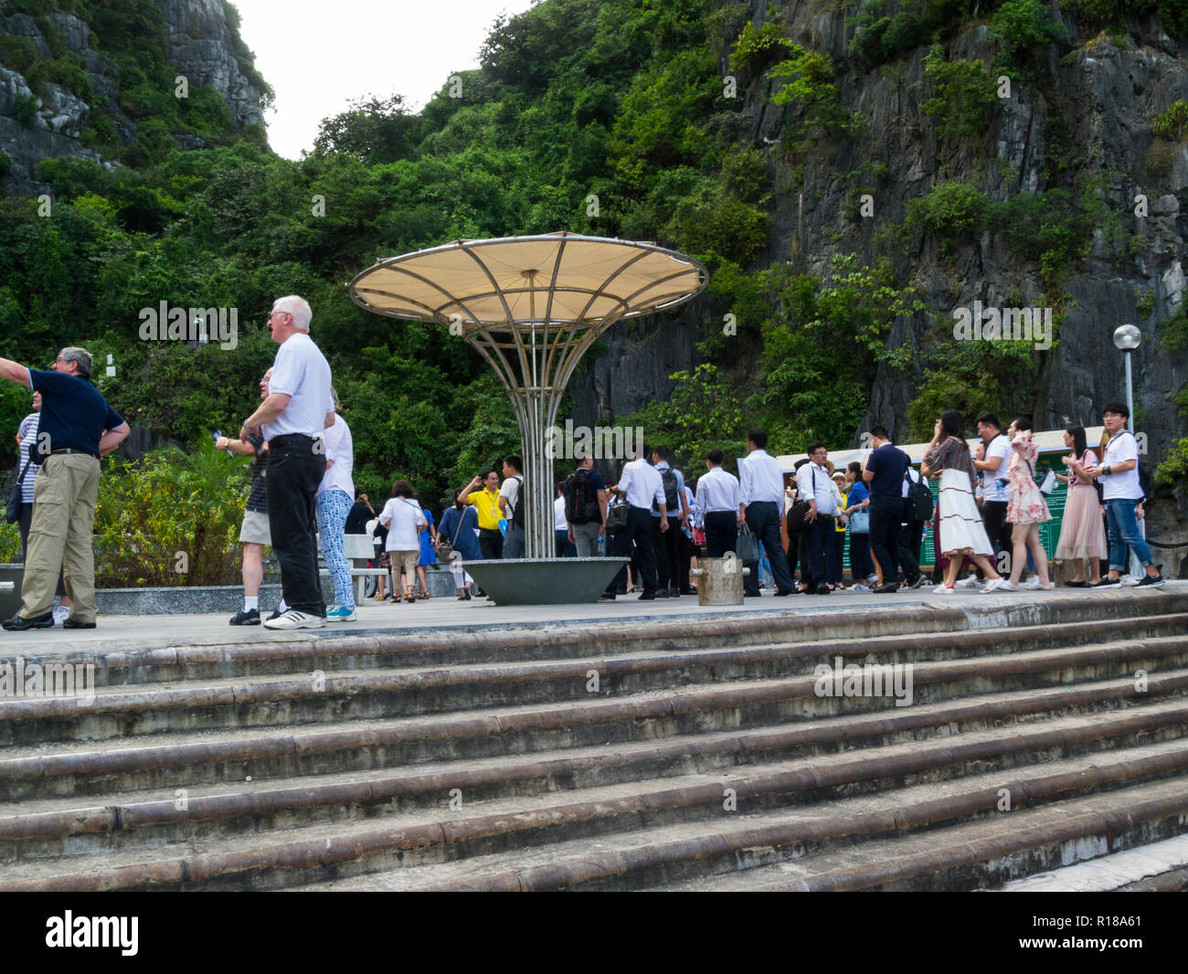 Tourists off junk cruise boats to visit one of caves in limestone cliffs Halong Bay South China Sea Vietnam Asia - Stock Image