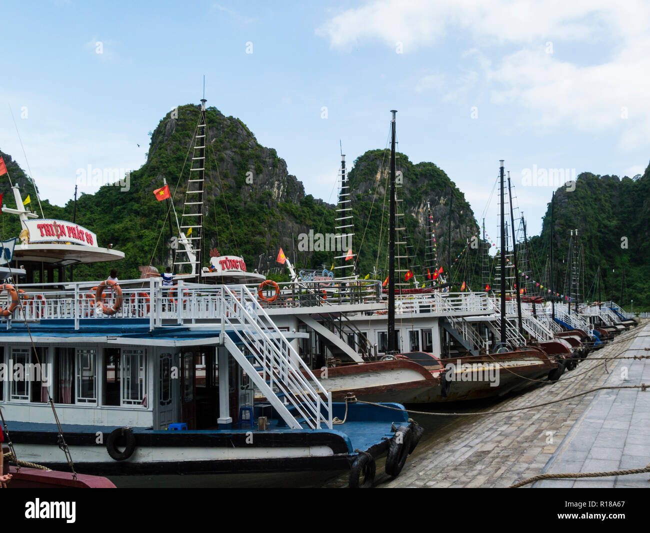 Junk Cruise boats moored for tourists to visit cave in limestone island peaks Halong Bay South China Sea Vietnam Asia - Stock Image
