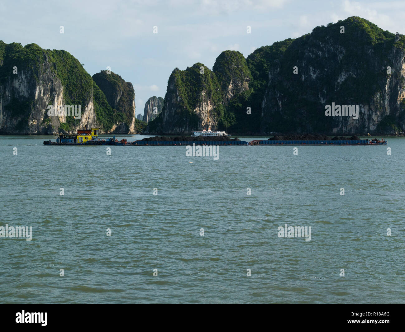 Tug pulling two barges filled with soil very low calm water travelling along Halong Bay South China Sea Vietnam Asia front of dramatic limestone cliff - Stock Image