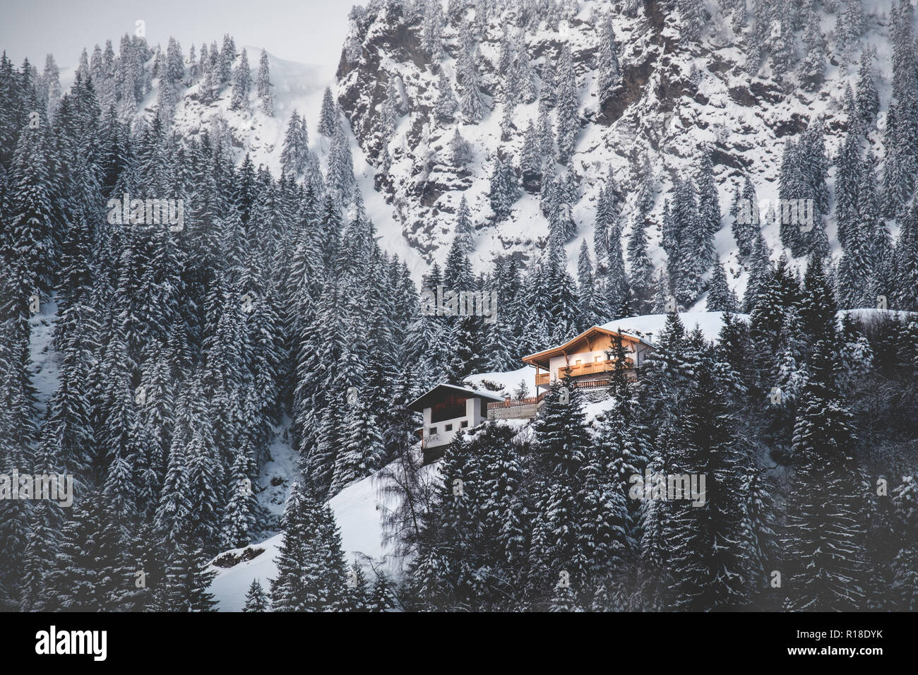 cabin illuminates snow covered valley misty firs mountain first light dawn - Stock Image