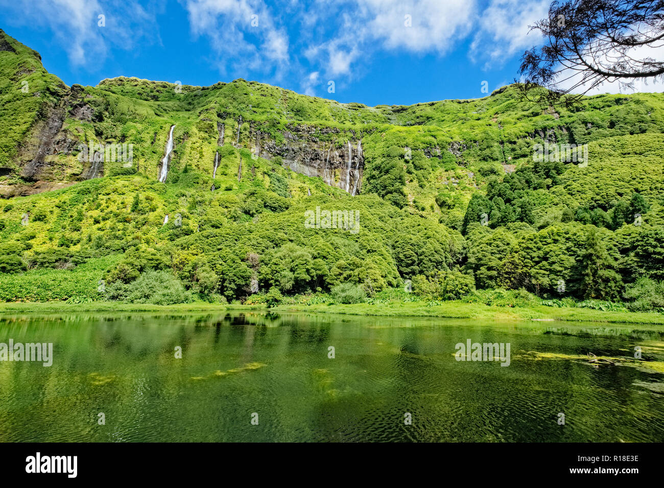 Flores Island, Portugal. July 28, 2018 Waterfalls flows into a green lagoon Stock Photo