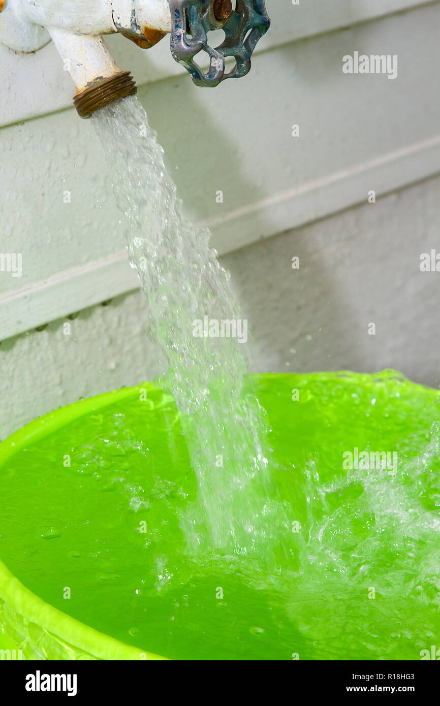 Water gushing out of outdoor spigot on home into to green pail. - Stock Image