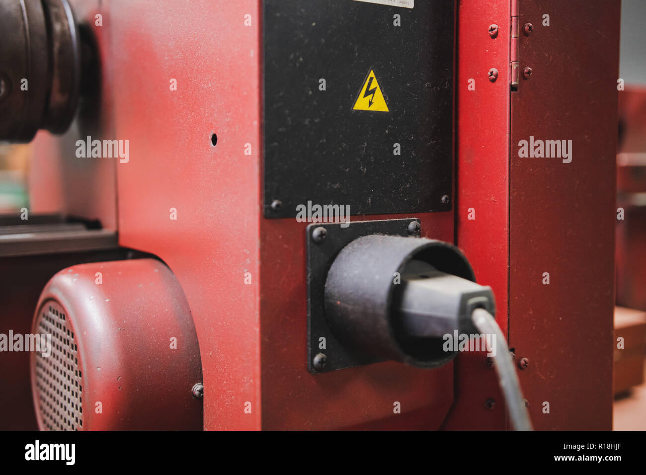High voltage warning sticker at the back of a power tool in workshop - Stock Image