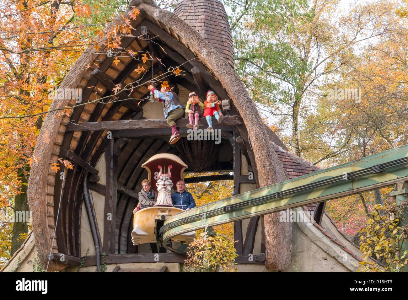 Grand parents sitting in monorail ride in entertainment park Efteling. Volk van Laaf attraction. - Stock Image