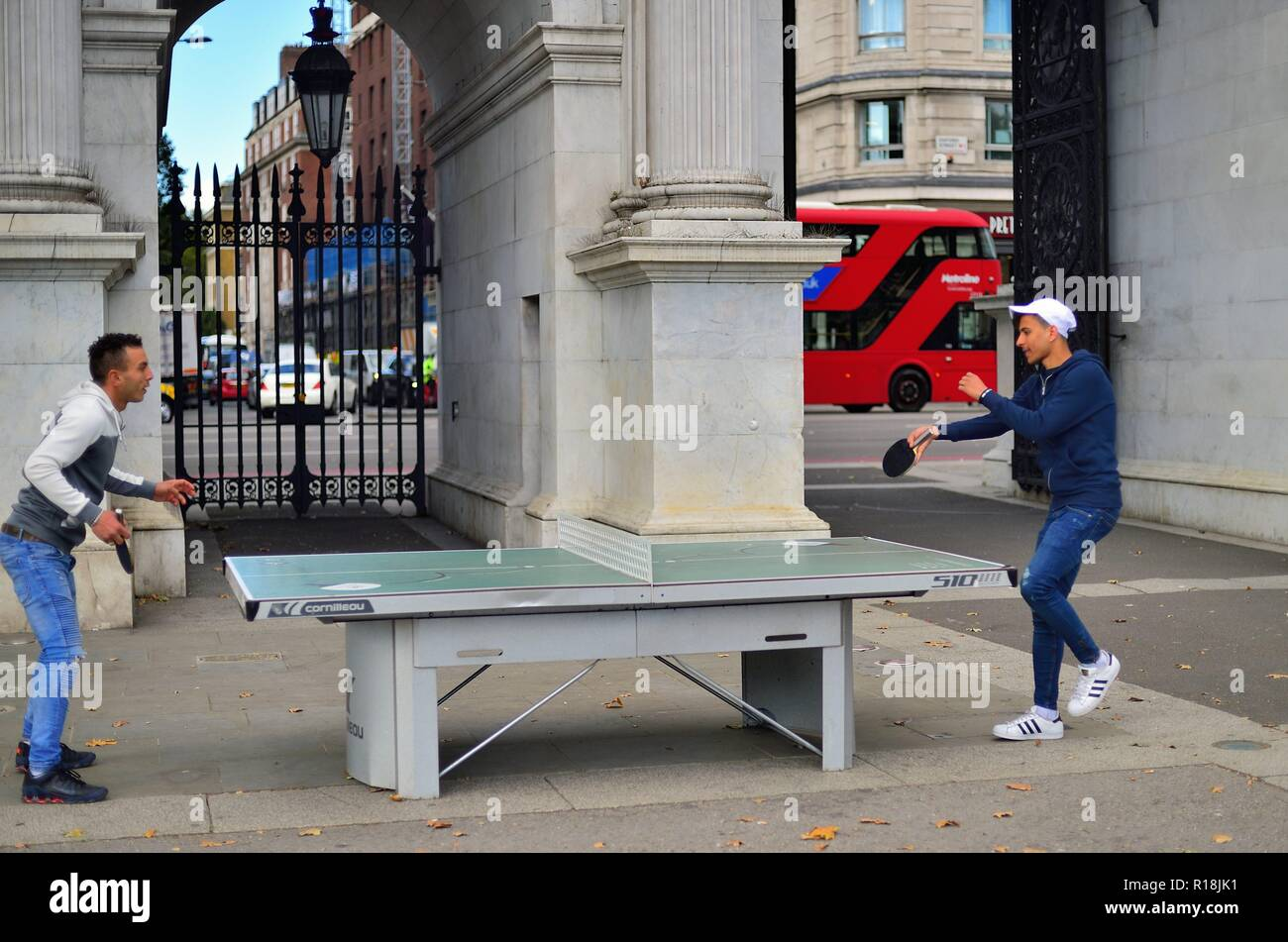 London, England, United Kingdom. Two men enjoy a ping-pong contest at the foot of Marble Arch. - Stock Image