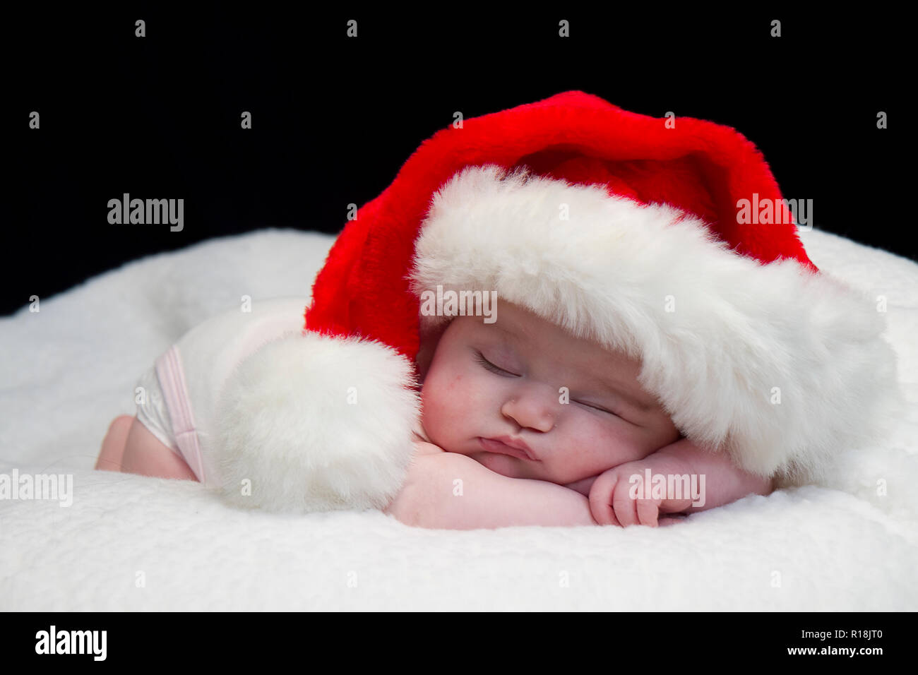 Infant Baby girl posing while sleeping in some with Santa hat and others with blanket.  Also one with angel wings and another in metal bath tub crying. Stock Photo