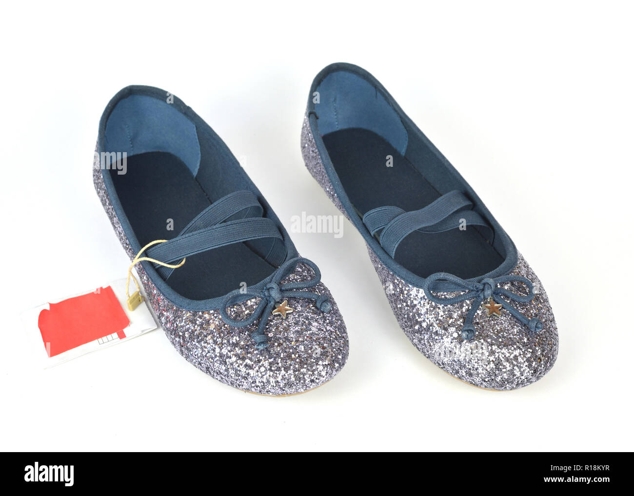 Shimmer silver blue ballerina flat shoes with crossed elastic drawstrings and a price tag on white background - Stock Image
