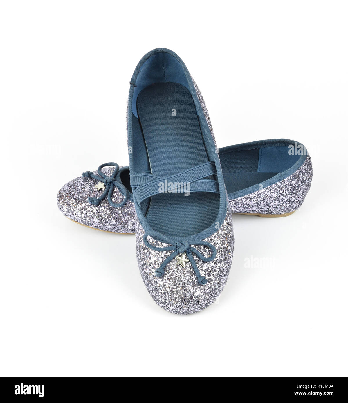 Shimmer silver blue ballerina flat shoes a small bow and with crossed elastic drawstrings on white background - Stock Image