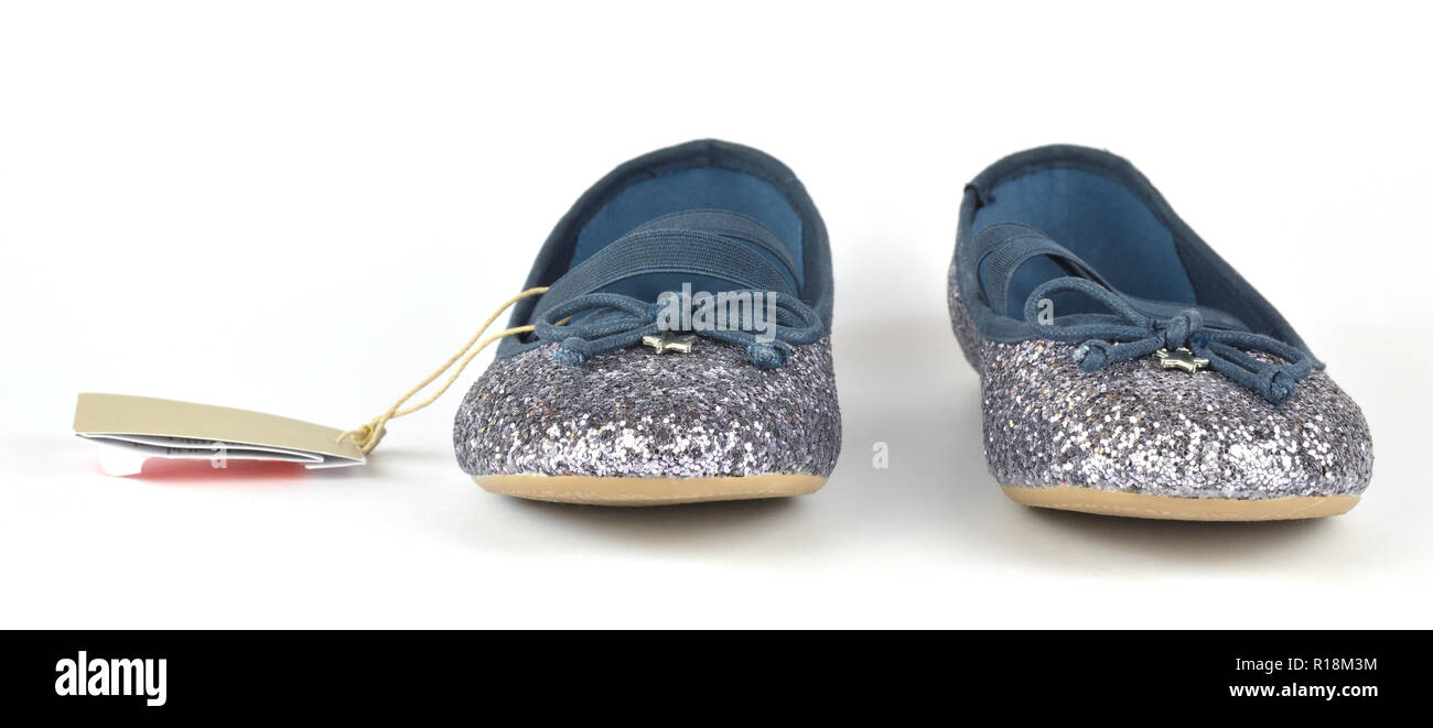 Comfortable shimmer silver blue ballerina flat shoes with a small bow and a rubber outsole on white background - Stock Image