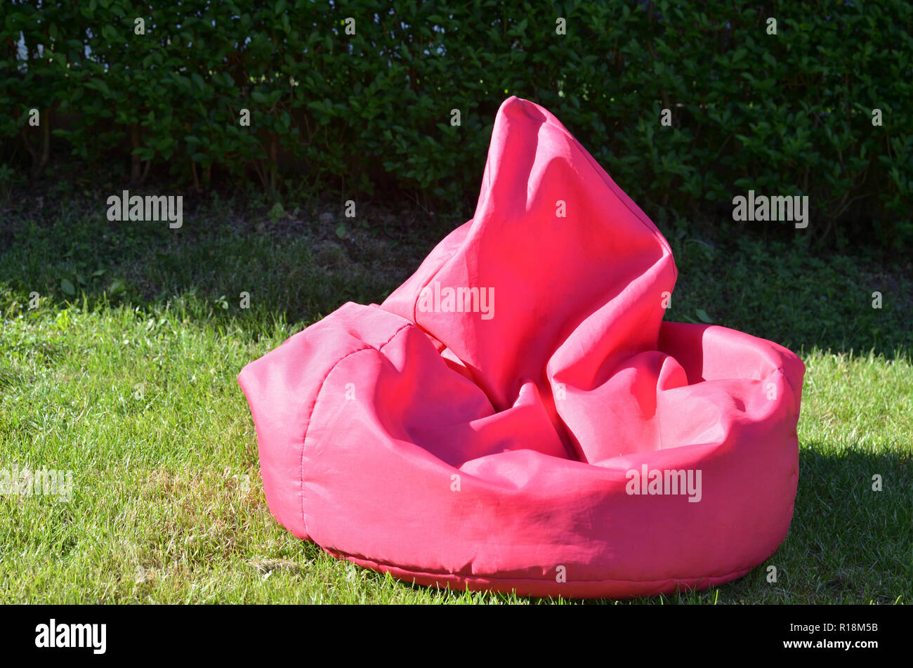 Pink bean bag on a garden lawn - Stock Image