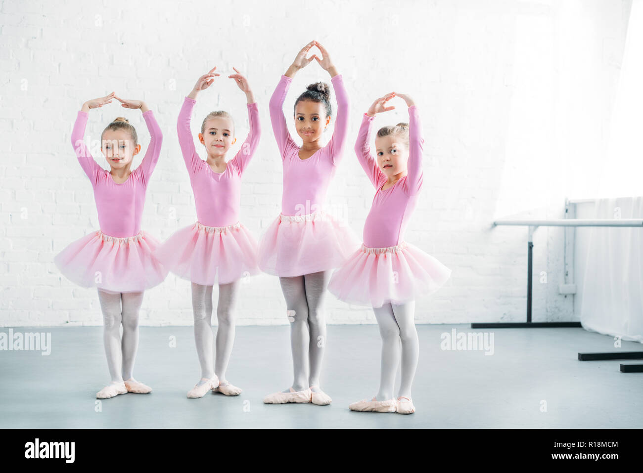 beautiful multiethnic kids in pink tutu skirts practicing ballet together - Stock Image