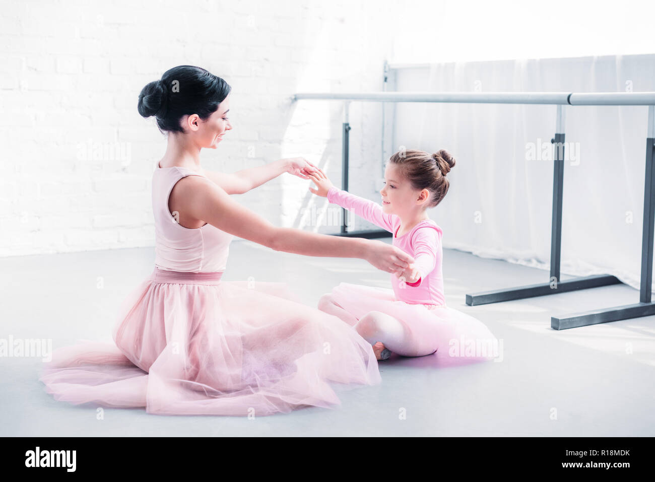 side view of ballet teacher and little student in pink tutu skirts sitting and holding hands while training in ballet school - Stock Image