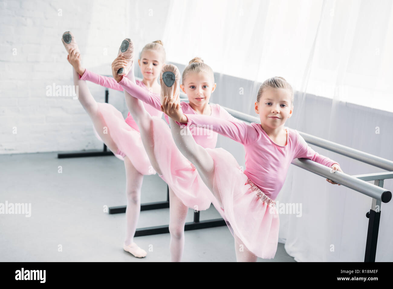 adorable kids in pink tutu skirts practicing ballet and looking at camera in ballet school - Stock Image