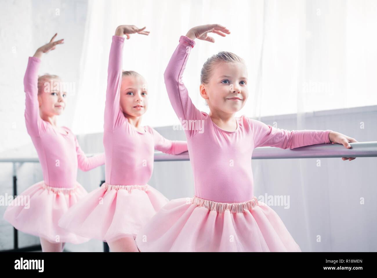 adorable smiling children in pink tutu skirts dancing in ballet studio - Stock Image