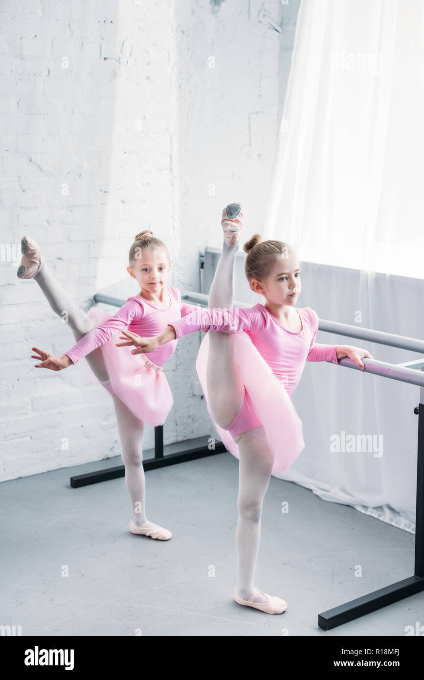 cute little kids in pink tutu skirts stretching and dancing in ballet school - Stock Image
