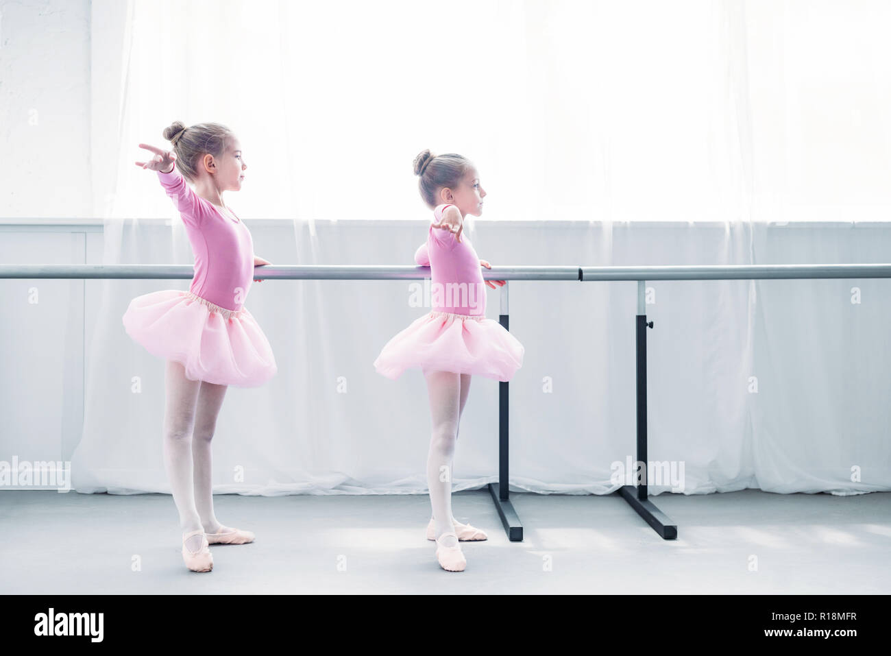 side view of beautiful little kids in pink tutu skirts practicing ballet in ballet studio - Stock Image