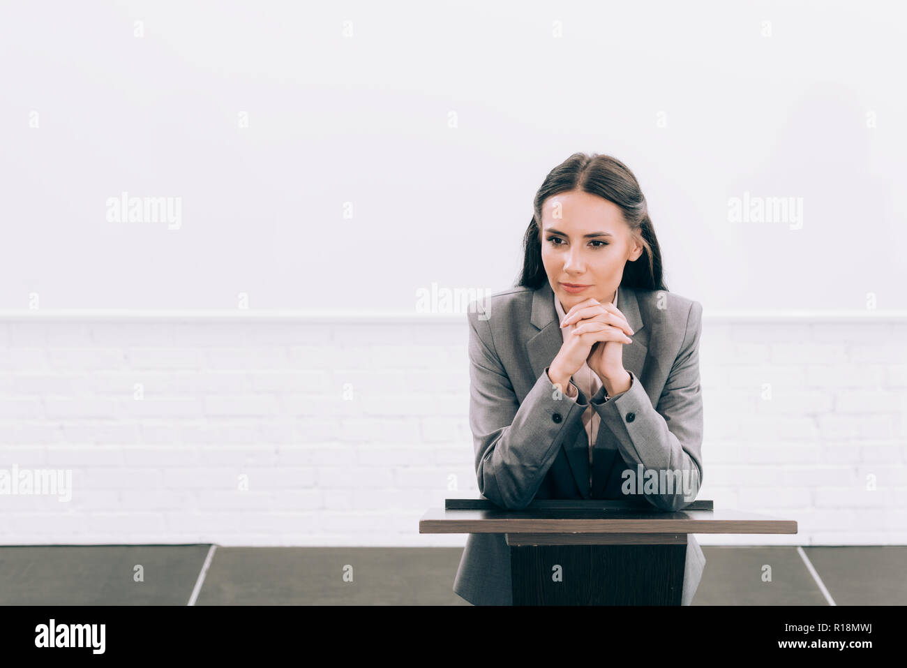 attractive lecturer leaning on podium tribune during seminar in conference hall - Stock Image