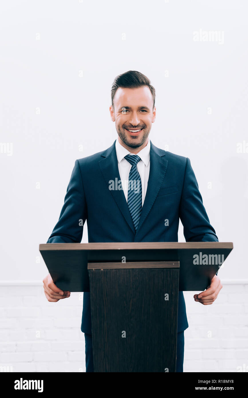 smiling lecturer standing at podium tribune during seminar in conference hall - Stock Image