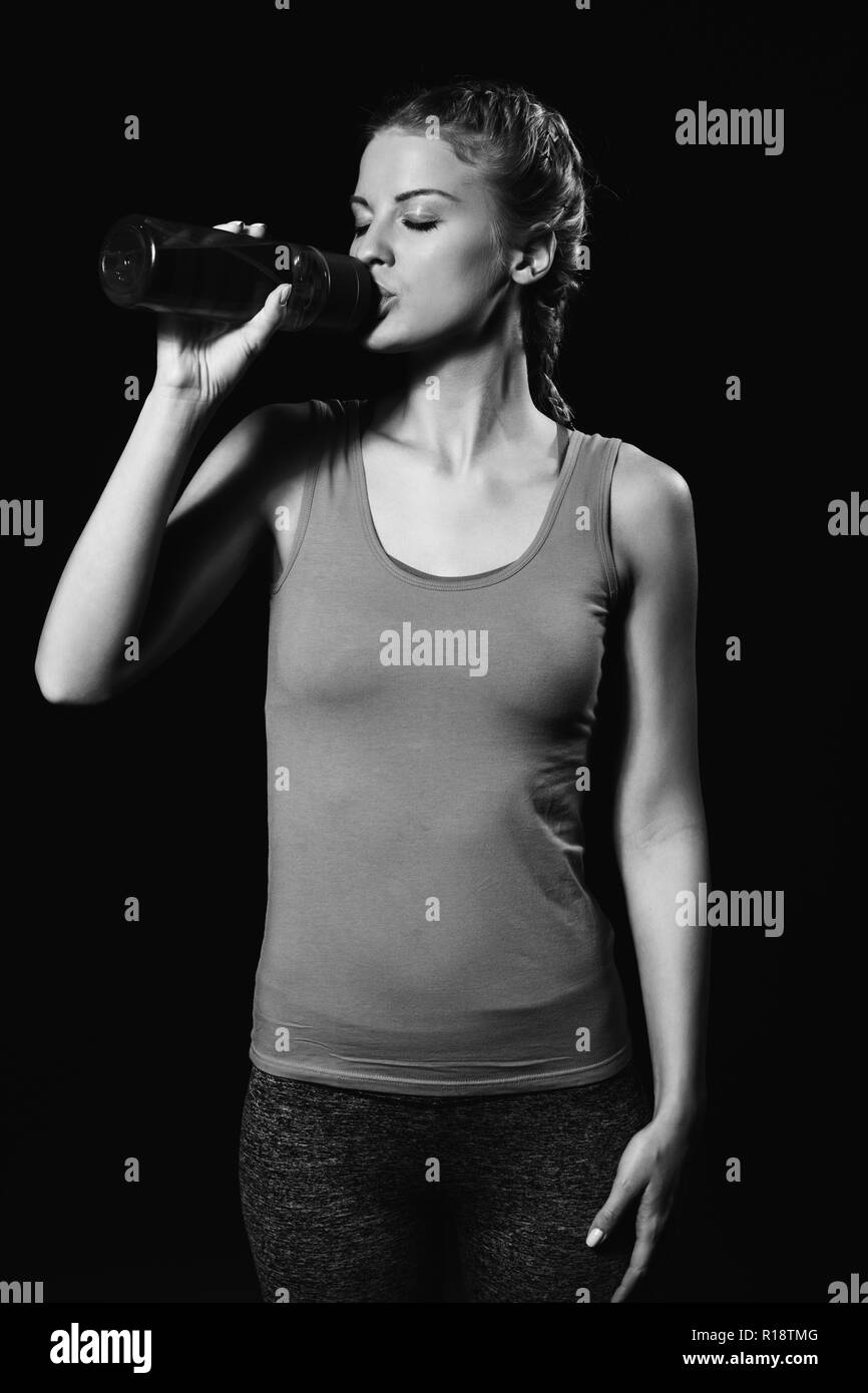 Beautiful blonde woman is drinking water after exercise. - Stock Image